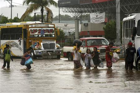 People carry their belongings as they evacuate from a flooded neighborhood in Acapulco