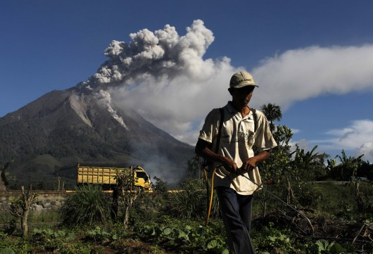 A farmer sprays pesticide as Mount Sinabung spews ash into the air at Sibintun village in Karo