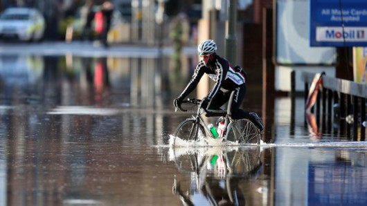 A cyclist braves a flooded road in Surrey