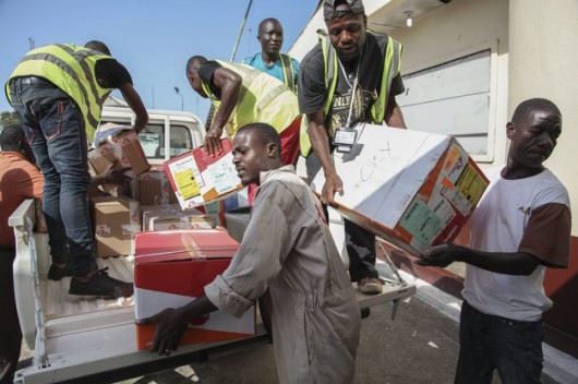 Liberyjczycy rozładowują transport ochronnych ubrań i materiałów edukacyjnych nt. wirusa Ebola