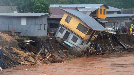 A house collapses into a river in the Solomon Islands after flooding