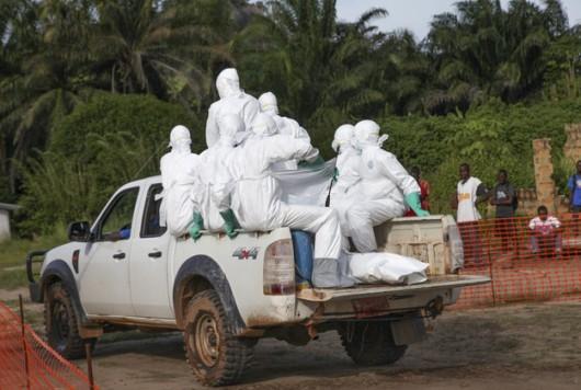 Liberyjscy pracownicy ochrony zdrowia w specjalnych kombinezonach jadą pochować kobietę, która zmarła na gorączkę krwotoczną Ebola /AHMED JALLANZO /PAP/EPA