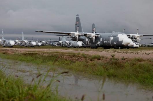 Rzędy transportowców C-130 Hercules gotowych na ewentualne przywrócenie do służby. Zdjęcie wykonane po bardzo rzadkim zjawisku w tym miejscu - ulewie