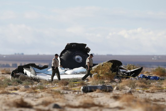 Sheriff's deputies look at a piece of debris near the crash site of Virgin Galactic's SpaceShipTwo near Cantil