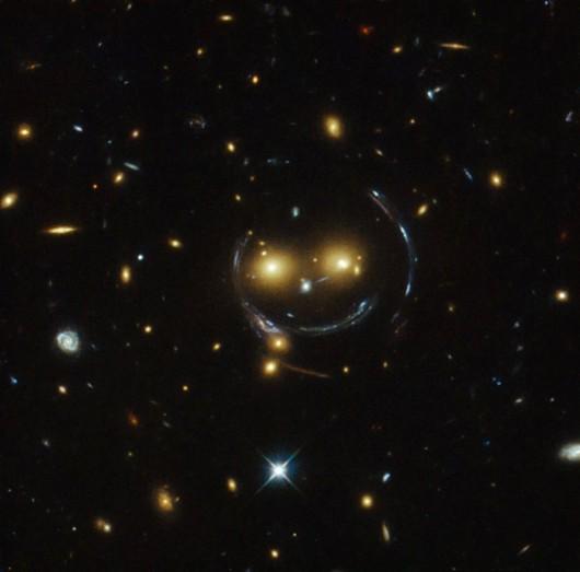 Gromada galaktyk i soczewkowanie grawitacyjne jak uśmiechnięta buźka