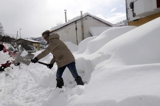 Kobieta odgarnia śnieg przed swoim domem w Kastylii-Leon na północy Hiszpanii /J. CASARES /PAP/EPA