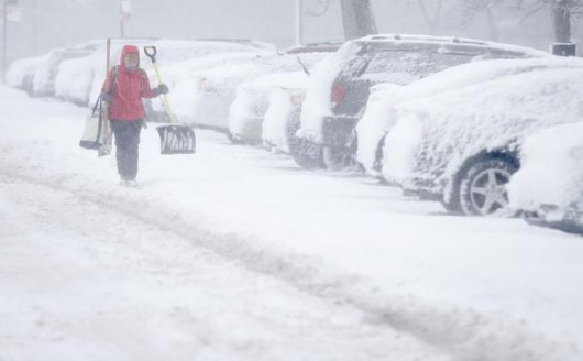 A woman carries a shovel through parking lot during blizzard conditions in Chicago