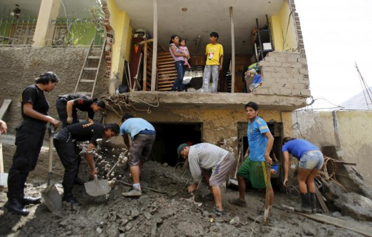 People remove mud and rocks after a massive landslide in Chosica