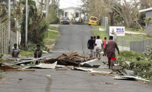 Local residents sit near debris on a road outside a hospital after Cyclone Pam hit Port Vila, the capital city of the Pacific island nation of Vanuatu
