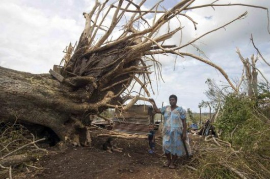 A woman and her child stand next to tree that nearly fell on their home in Port Vila
