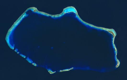 Współczesne zdjęcie satelitarne atolu Bikini. W lewym górnym rogu widać dużą dziurę w rafie, którą pozostawił po sobie test Bravo. Bunkier dla naukowców mieścił się na wysepce w prawym dolnym rogu