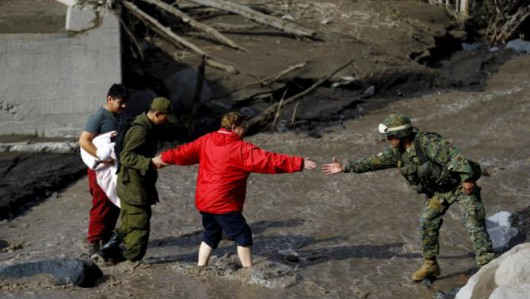 Soldiers help a resident to cross a river after lahar from Calbuco Volcano at Correntoso near Chamiza, April 25, 2015. Ash from the Chilean volcano Calbuco, which erupted without warning this week, reached as far as southern Brazil on Saturday and prompted some airlines to cancel flights to the capitals of Chile, Argentina and Uruguay. REUTERS/Ivan Alvarado