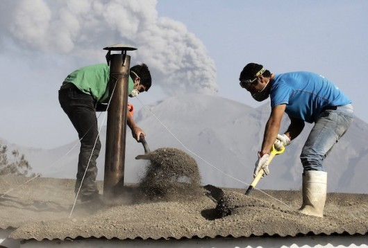 epaselect epa04719569 Men remove ash from a rooftop as the Calbuco volcano continues to spew clouds of ash in Ensenada village, in the region of Los Lagos, southern Chile, 24 April 2015. The Calbuco volcano in southern Chile erupted 22 April after lying dormant for 43 years. The Chilean town of Ensenada was covered in 50 centimetres of ash, and about 4,000 people needed to be evacuated, the Chilean National Emergency Office (ONEMI) said on 23 April. Schools in the area around the volcano were closed.  EPA/FELIPE TRUEBA
