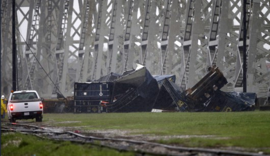 Train cars are seen beneath the Huey P. Long Bridge, which crosses over the Mississippi River, after they toppled off the bridge from high winds in Jefferson Parish, La., just outside New Orleans, Monday, April 27, 2015. More than 200,000 homes and businesses lost power and at least four cars carrying freight containers were blown off the approach to the Huey P. Long Bridge outside New Orleans as a line of severe thunderstorms moved across southeast Louisiana. None of the freight containers held hazardous cargo, and nobody was injured.  (AP Photo/Gerald Herbert)