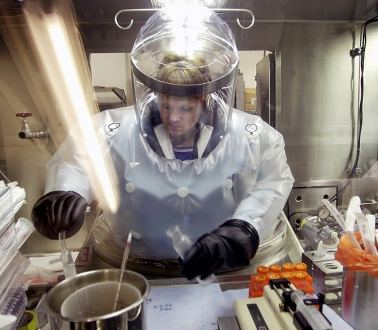 FILE - In this May 11, 2003, file photo, Microbiologist Ruth Bryan works with BG nerve agent simulant in Class III Glove Box in the Life Sciences Test Facility at Dugway Proving Ground, Utah. The specialized airtight enclosure is also used for hands-on work with anthrax and other deadly agents. The Centers for Disease Control and Prevention said it is investigating what the Pentagon called an inadvertent shipment of live anthrax spores to government and commercial laboratories in as many as nine states, as well as one overseas, that expected to receive dead spores. (AP Photo/Douglas C. Pizac, File)