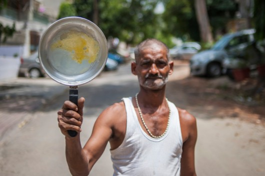 NEW DELHI, INDIA - MAY 29: Ajay Yadav, 49, shows the omelette on a frying pan on May 29, 2015 in New Delhi, India.  49 YEAR OLD Ajay Yadav is making a perfect use of the rising temperature in Delhi. The slum dweller in South Delhi was seen cooking up an omelette on a pan, under the intense mid day sun on Friday afternoon.  Yadav had left the pan out in the sun for over an hour and it was heated enough to make an omelette on it. The temperatures are so unbearable in Delhi that Yadav sleeps with a wet shirt. Thousands of people like Yadav, who live in makeshift shanties, are grappling with the unprecedented heat wave. The ongoing torrid heat wave has killed over 1,400 people across many Indian states, with most deaths being reported from Andhra Pradesh and Telangana. According to a government release issues earlier this week, most of the victims have been construction workers, the elderly or the homeless. The meteorological department has issued heatwave signalling high chances fatality with temperatures inching upwards of 45°C and conditions worsened by constant dry, sweltering winds.  PHOTOGRAPH BY Arkaprava Ghosh / Barcroft India  UK Office, London. T +44 845 370 2233 W www.barcroftmedia.com  USA Office, New York City. T +1 212 796 2458 W www.barcroftusa.com  Indian Office, Delhi. T +91 11 4053 2429 W www.barcroftindia.com