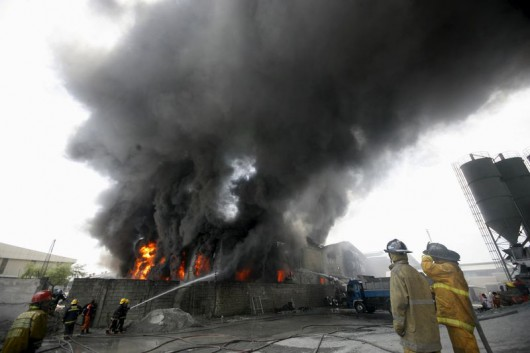 Firefighters attempt to control a raging fire at a factory that manufactures slippers in Valenzuela City