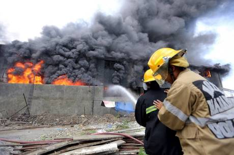 Firefighters try to control a raging fire at a factory in Valenzuela City, north of Manila