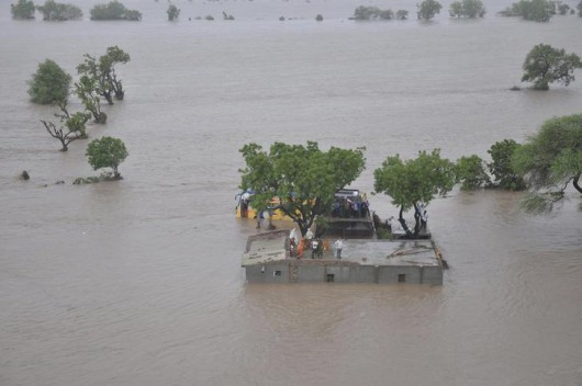 An aerial view shows flood victims standing atop their submerged houses in Amreli district of Gujarat, India, June 24, 2015. At least 24 people have died due to heavy rains and flood related incidents in the western state of Gujarat, local media reported. REUTERS/Indian Air Force/Handout