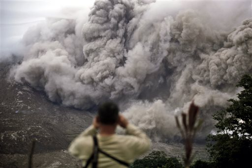A man watches as Mount Sinabung releases pyroclastic flows in Tiga Serangkai, North Sumatra, Indonesia, Tuesday, June 16, 2015. Authorities have been closely monitoring Sinabung since June 2 when its status was raised to the highest alert level due to the growing size of its lava dome. (AP Photo/Binsar Bakkara)