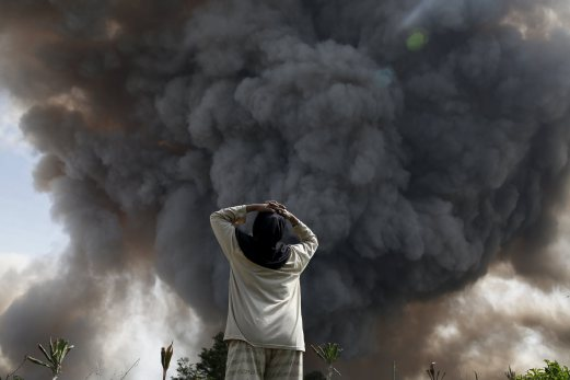 A resident reacts as Mount Sinabung volcano spews ash during an eruption at Tiga Serangkai village in Karo Regency, North Sumatra province, Indonesia, June 24, 2015. More than 10,000 people from 12 villages, who are living around the slopes of Mount Sinabung, left their homes and moved to refugee camps, local media reported on Friday. REUTERS/Beawiharta