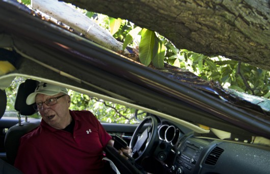 Robert Mole retrieves belongings from his car hours after a severe storm in Jackson, Mich., on Tuesday, June 23, 2015.  A series of severe thunderstorms that pushed damaging winds and tornados into several parts of Michigan wrecked homes and knocked out power to thousands of people, officials said Tuesday. (J. Scott Park/The Jackson Citizen Patriot via AP) ALL LOCAL TELEVISION OUT; LOCAL TELEVISION INTERNET OUT