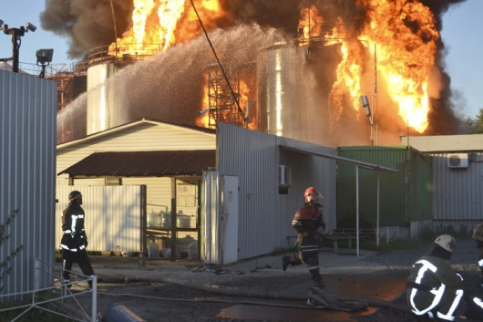 Firefighters work to extinguish fire at a fuel depot near Vasylkiv in Kiev region, Ukraine, June 8, 2015. Emergency services are battling to prevent the spread of a deadly fuel depot fire outside Kiev, the head of the emergency services said on Tuesday, and three firemen were reported missing after the blaze triggered a powerful explosion. The fire burned overnight and by morning had spread to at least 16 tanks, most of them storing petrol, sending a huge pall of smoke over the area surrounding the depot near Vasylkiv, 30 km (19 miles) from Kiev. Picture taken June 8, 2015. REUTERS/Ministry of Emergencies of Ukraine/Handout via Reuters ATTENTION EDITORS - THIS PICTURE WAS PROVIDED BY A THIRD PARTY. REUTERS IS UNABLE TO INDEPENDENTLY VERIFY THE AUTHENTICITY, CONTENT, LOCATION OR DATE OF THIS IMAGE. FOR EDITORIAL USE ONLY. NOT FOR SALE FOR MARKETING OR ADVERTISING CAMPAIGNS. NO SALES. NO ARCHIVES. THIS PICTURE IS DISTRIBUTED EXACTLY AS RECEIVED BY REUTERS, AS A SERVICE TO CLIENTS.