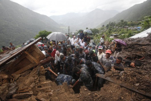 Nepalese policemen search for bodies of victims from the debris after a landslide in Lumle village, about 200 kilometers (125 miles) west of Kathmandu, Nepal, Thursday, July 30, 2015. Landslides in a mountain area of Nepal buried three villages Thursday, killing several people, authorities said.(AP Photo/Niranjan Shrestha)