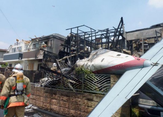 The tail section of a crashed light plane (R) and burning house are seen after the plane went down in a residential area and burst into flames, in Chofu, outskirt of Tokyo, in this photo taken by Kyodo July 26, 2015. Mandatory credit REUTERS/Kyodo