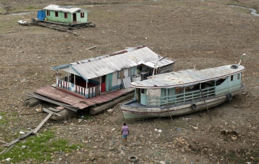 Two houseboats and a boat (R) lie at the bottom of a branch of the Rio Negro, a tributary to the Amazon river, in the city of Manaus, Brazil, October 19, 2015.  A severe drought has pushed river levels in Brazil's Amazon region to lows, leaving isolated communities dependent on emergency aid and thousands of boats stranded on parched riverbeds. REUTERS/Bruno Kelly