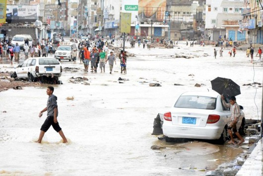 HADRAMOUT, YEMEN - NOVEMBER 03: Yemenis walk past the vehicles damaged by wind and heavy rain-caused floodwaters, as a result of Cyclone Chapala generated in the Arabian Sea, on the shore of Hadramout, Yemen on November 03, 2015. (Photo by Resid bin Sebrak/Anadolu Agency/Getty Images)
