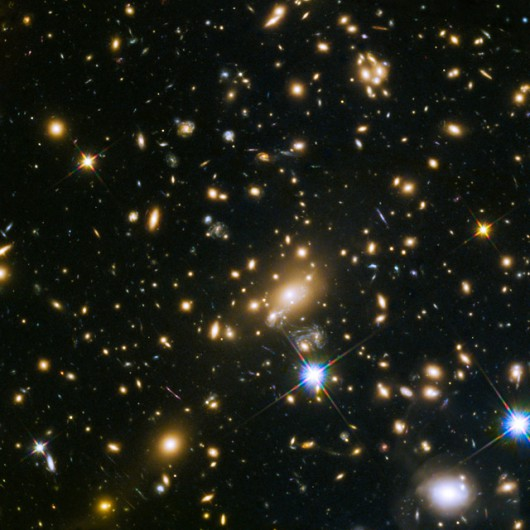 This image shows the huge galaxy cluster MACS J1149.5+223, whose light took over 5 billion years to reach us. The huge mass of the cluster and one of the galaxies within it is bending the light from a supernova behind them and creating four separate images of the supernova, shown clearly in this annotated image. The light has been magnified and distorted due to gravitational lensing and as a result the images are arranged around the elliptical galaxy in a formation known as an Einstein cross.