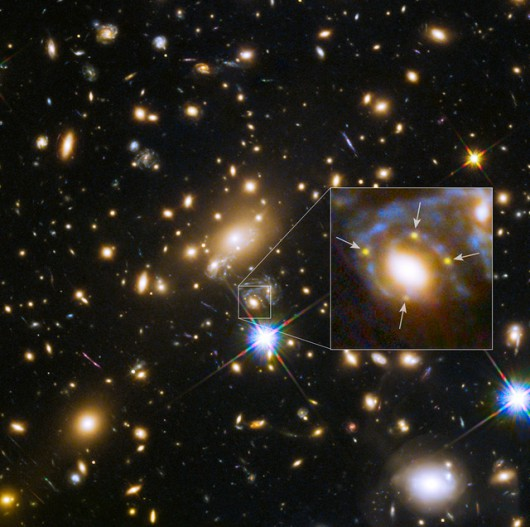 This image shows the huge galaxy cluster MACS J1149+2223, whose light took over 5 billion years to reach us. The huge mass of the cluster and one of the galaxies within it is bending the light from a supernova behind them and creating four separate images of it. The light has been magnified and distorted due to gravitational lensing and as a result the images are arranged around the elliptical galaxy in a formation known as an Einstein cross. A close-up of the Einstein cross is shown in the inset.