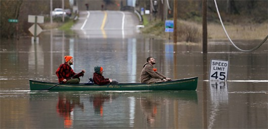 A group of men paddle a canoe across a flooded roadway along the Snoqualmie River near the peak of the river's height there, Wednesday, Nov. 18, 2015, in Carnation, Wash. Cleanup crews took to the streets Wednesday in Washington state after a powerful storm killed three people, cut power to more than 350,000 residents and flooded rivers. The winds on Tuesday exceeded 100 mph in some areas of the Inland Northwest, where fallen trees were blamed for the deaths. (AP Photo/Elaine Thompson)