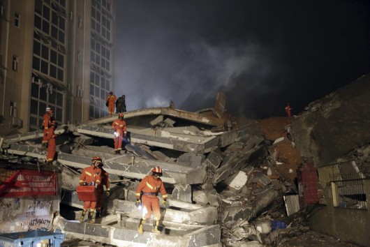 Rescuers search for survivors amongst collapsed buildings in the aftermath of a landslide in Shenzhen in south China's Guangdong province Sunday Dec. 20, 2015. The landslide collapsed and buried buildings at and around an industrial park in the southern Chinese city of Shenzhen on Sunday, leaving many missing, authorities said. (Color China Photo via AP) CHINA OUT