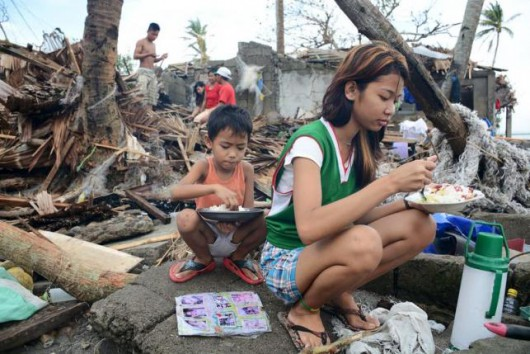 Residents eat outside of their damaged shanties after strong winds and heavy rains brought by typhoon Melor battered Barcelona town, Sorsogon province, central Philippines