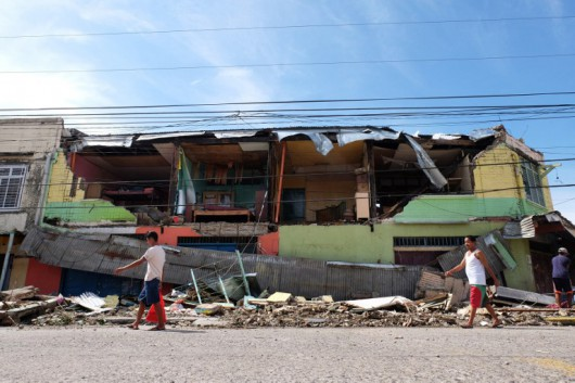 Residents walk past a house destroyed by typhoon Melor after it hit Bulan town, Sorsogon province, south of Manila on December 15, 2015. Tattered lanterns, festive lights and tin roofs littered towns in the central Philippines on December 15 after Typhoon Melor swept through, killing at least four people and leaving millions without power ahead of Christmas. AFP PHOTO/Charism Sayat / AFP / Charism SAYAT