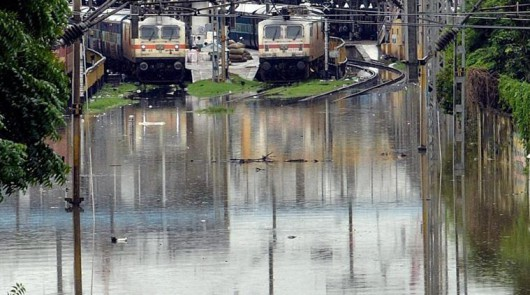 Chennai: Trains stand stranded at a railway station near flooded tracks after heavy rains in Chennai Wednesday. PTI Photo (PTI12_2_2015_000347B)