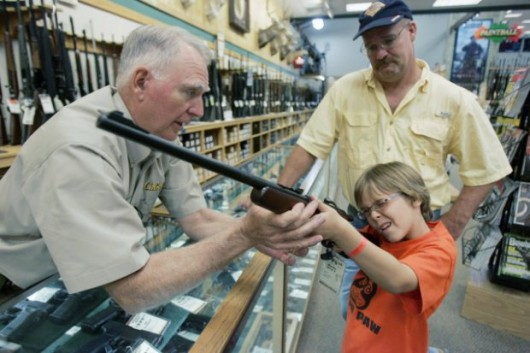 RNPS IMAGES OF THE YEAR 2008 Hunter McConathy (C), 7, holds a hunting rifle with a short stock as his father Bryan (R) and Cabela's salesman Russ Duncan (L) watch him at the Cabela's store in Fort Worth, Texas June 26, 2008. Individual Americans have a right to own guns, the Supreme Court ruled on Thursday for the first time in history, striking down a strict gun control law in the U.S. capital. REUTERS/Jessica Rinaldi (UNITED STATES) Siedmioletni McConathy trzyma broñ myœliwsk¹ w sklepie,