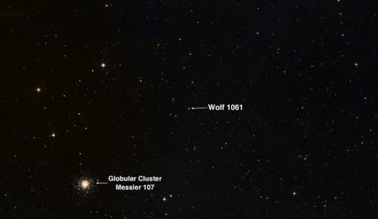 Obraz nieba w gwiazdozbiorze Wężownika w rejonie gwiazdy Wolf 1061 i gromady gwiazd Messier 104