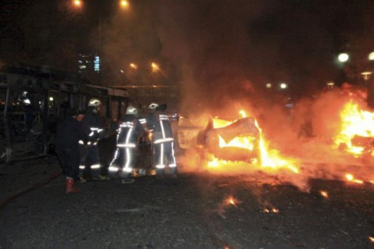 Emergency personnel work near a burning vehicle after an explosion in Ankara