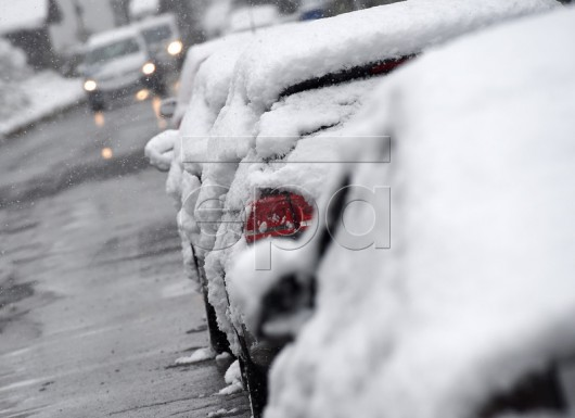 epa05276384 A row of snow covered vehicles are seen after a snowfall in Garmisch-Partenkirchen, Bavaria, Germany, 25 April 2016 .  EPA/ANGELIKA WARMUTH