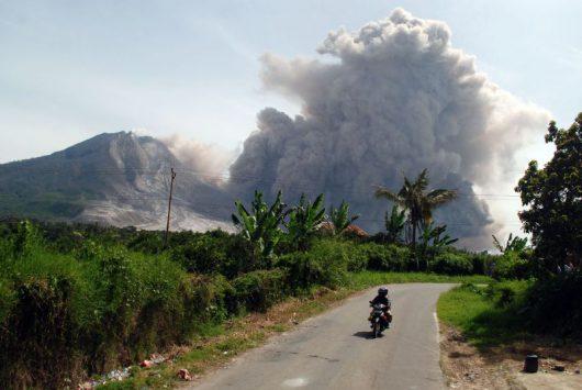 Pengendara sepeda motor melintas dengan latar belakang Gunung Sinabung yang tengah meluncurkan awan panas guguran kubah lava Gunung Sinabung di Karo, Sumatera Utara, Rabu (24/6).