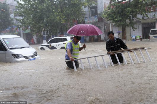 In this Tuesday, July, 19, 2016 photo released by Xinhua News Agency, a man helps a traffic policeman move away a barrier on a flooded road in Wanrong County, north China's Shanxi Province. China says dozens of people have died or gone missing since Monday in massive floods across the country's north. (Li Hongxiao/Xinhua via AP)