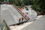 Members of Guatemalan emergency commission (CONRED) stand at a bridge that collapsed after heavy rains brought by Hurricane Earl at Menchor de Mencos, Guatemala, August 4, 2016. REUTERS/Luis Echeverria