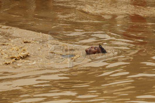 epa05450362 A Yemeni swims in floodwaters following a heavy rain in Sana'a, Yemen, 31 July 2016. EPA/YAHYA ARHAB