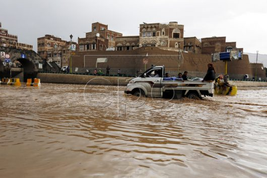 epa05450166 A Vehicle drives through a flooded road following heavy rains in the old city of Sana'a, Yemen, 31 July 2016. Torrential rain hit Sana'a and most parts of Yemen as summer temperatures soar. EPA/YAHYA ARHAB