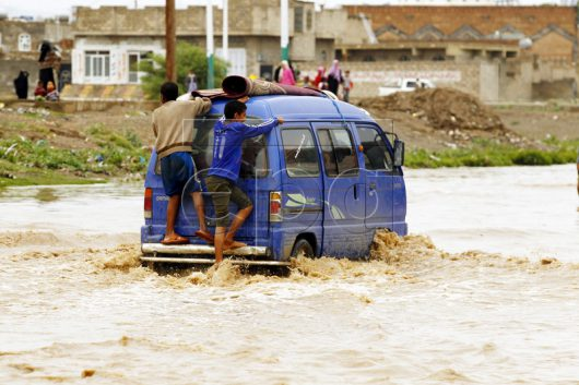 epa05450165 A minibus drives through a flooded road following heavy rains in Sana'a, Yemen, 31 July 2016. Torrential rain hit Sana'a and most parts of Yemen as summer temperatures soar. EPA/YAHYA ARHAB