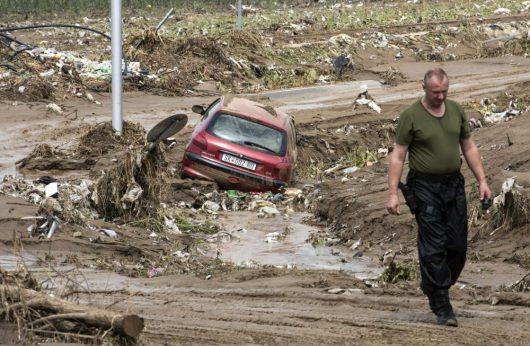 epa05461010 A police officer passes a vehicle swept in to a field near the ring road around Skopje, The Former Yugoslav Republic of Macedonia on 07 August 2016. At least 15 people have died in a rain storm that hit the Macedonian capital Skopje late on 06 August 2016 causing severe damage to roads, houses and infrastructure. Around 80 vehicles were caught in landslides the hit Skopje's ringroad which remains closed. EPA/GEORGI LICOVSKI Dostawca: PAP/EPA.