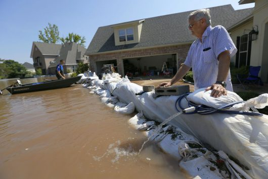 Tom Siskron IV, right, pauses as a pump works to remove water from his son's property caused by the flooding of the Red River, Thursday, June 11, 2015, in Shreveport, La.   Flooding from the swelling river put hundreds of homes and farmland underwater or in danger in rural northwest Louisiana, and state officials said Thursday that they would seek a federal disaster declaration to get help for residents.  (AP Photo/Jonathan Bachman)